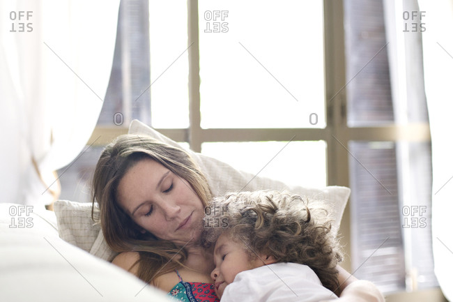 Mother and child napping on sofa at home
