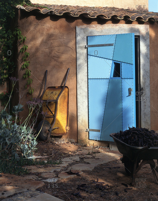 Wheelbarrow outside blue shed door