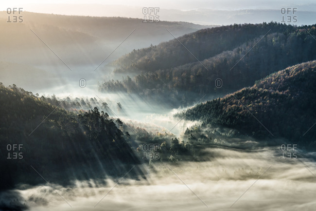 Sunrays and fog over forested hills in Germany