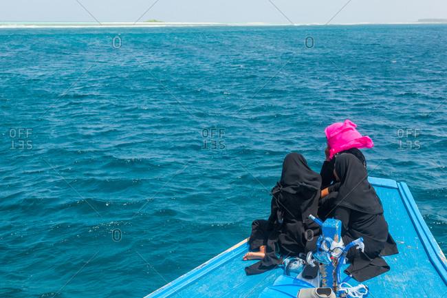 Three Muslim women ride a boat prow