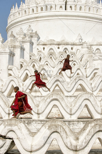 Myanmar, Southeast Asia - March 1, 2015: Three young monks playing on the terraces of Hsinbyume Pagoda, Mandalay