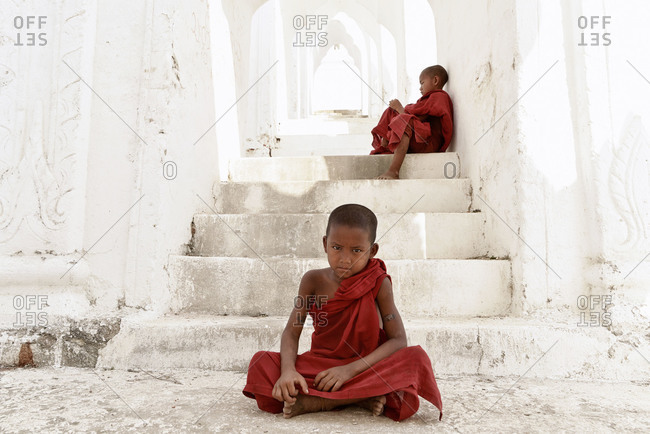 Myanmar, Southeast Asia - March 3, 2015: Young monks sitting in stairway at Hsinbyume Pagoda, Myanmar