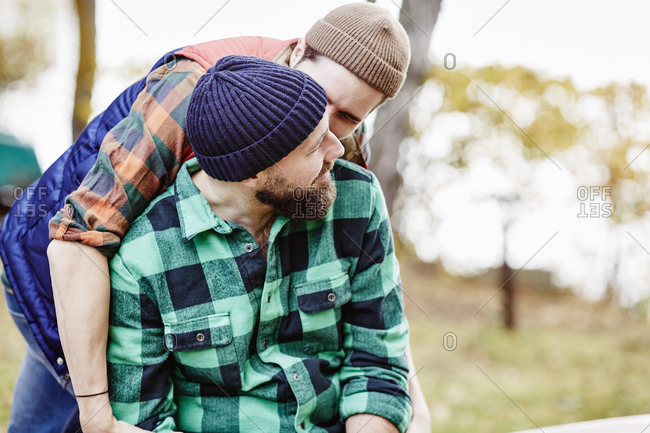 Man giving his boyfriend a peck on his check
