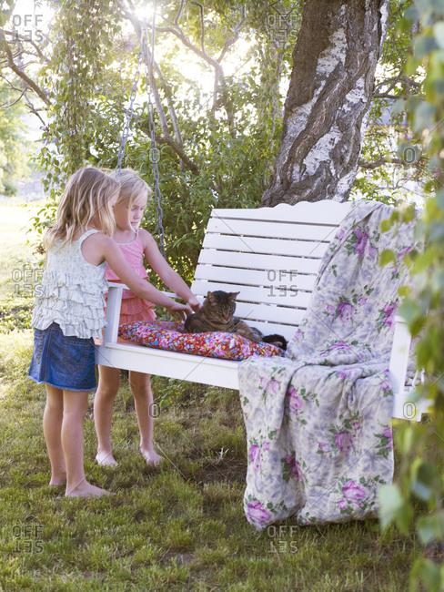 Girls stroking cat on hanging bench