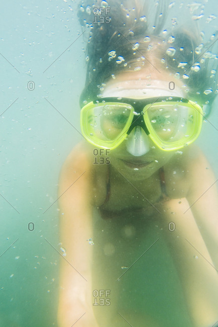 Girl swimming in scuba mask underwater