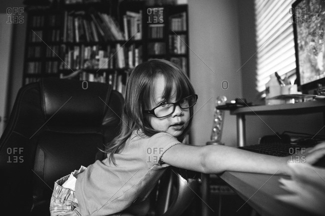 Little girl with tilted glasses sitting at computer