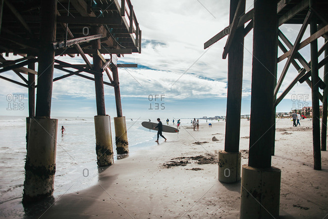 View through a pier of surfer and beachgoers