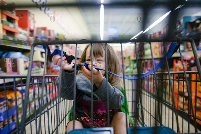 Young girl sitting in shopping cart plays with seat buckle