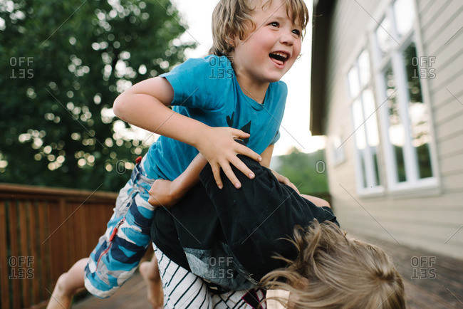 Little boy jumping on his brother's back