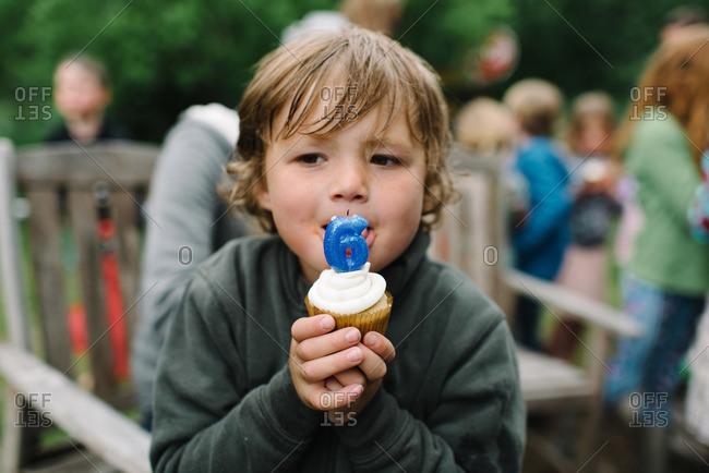 Little boy tasting a cupcake