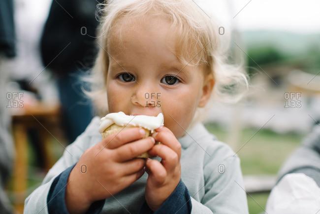 Little girl biting a cupcake