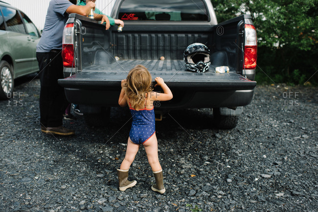 Little girl standing at a truck tailgate