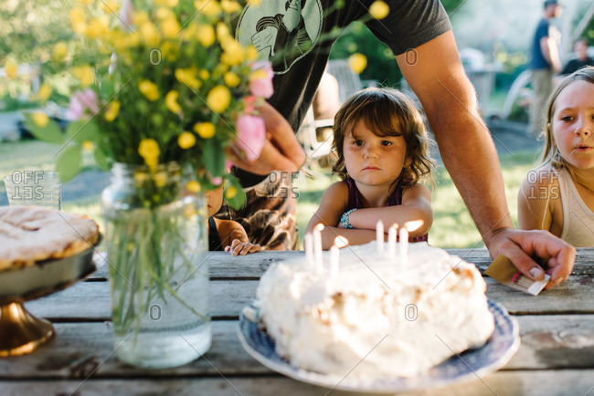 Little girl watching birthday cake candles being lit