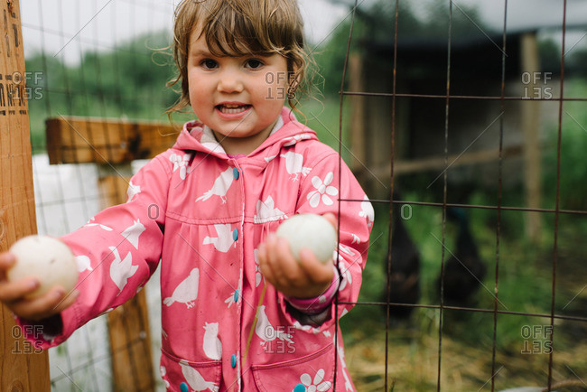 Little girl showing collected chicken eggs