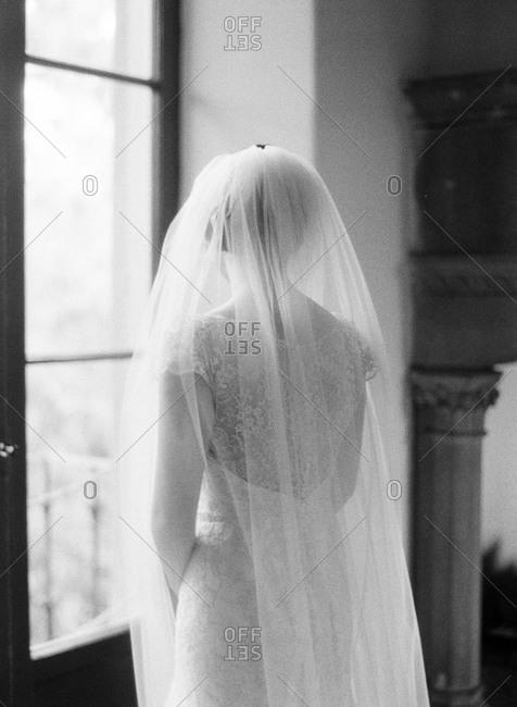 A bride stands near a window