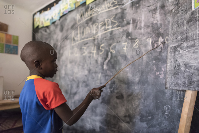 Jinja, Uganda - March 18, 2015: Student reciting numbers at chalkboard in school