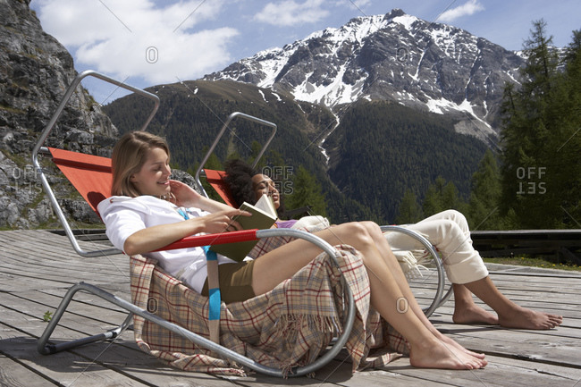 Two young women sitting on deck chairs on sun deck