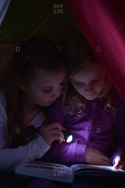 Two girls reading a book with a torch in their self-made cave