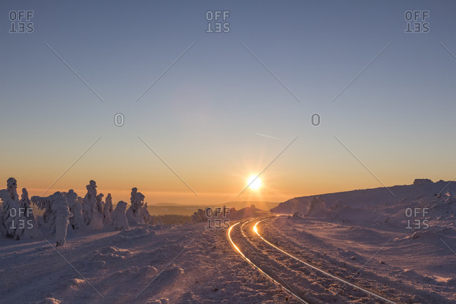 Rail tracks of Harz Narrow Gauge Railway in winter against the evening sun, Harz National Park