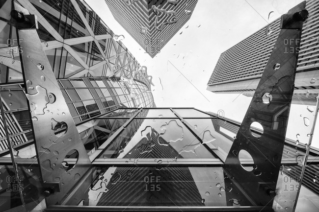 Upward view through rain-spattered glass of skyscrapers in Tokyo