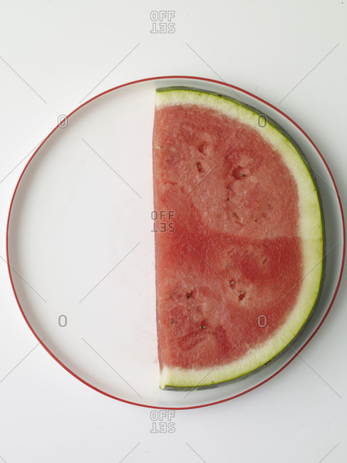 Half watermelon slice on a round plate