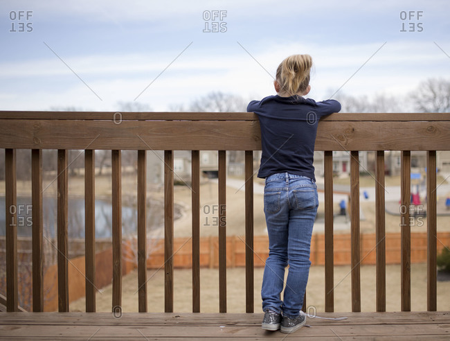Young girl staring over deck railing