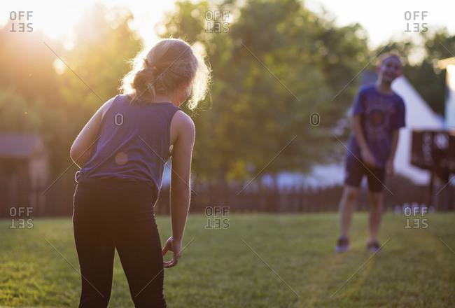 Two kids in a sun dappled summer yard