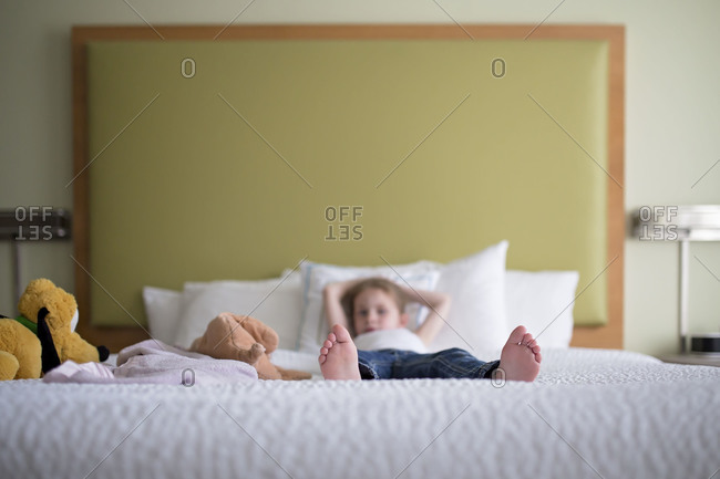 Kid lying barefoot on bed