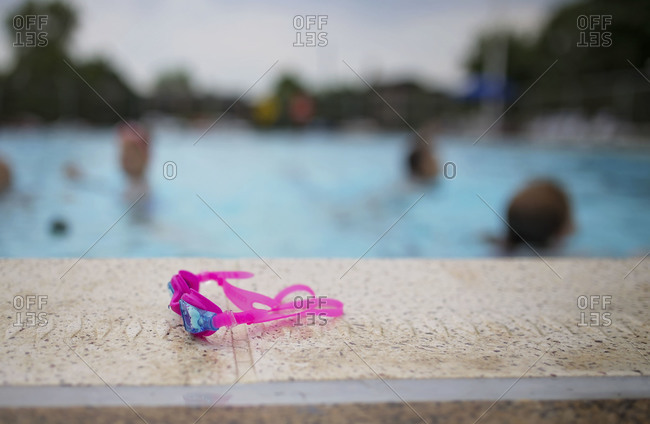 Goggles on the edge of a public pool