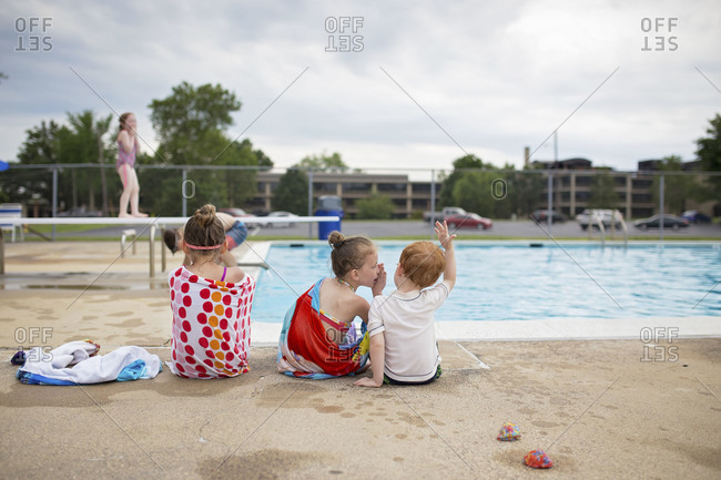 Three kids sitting poolside together