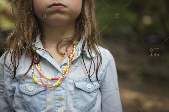 Girl wearing toy necklace in rural setting