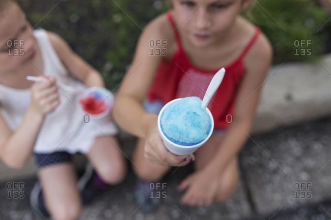 Two girls enjoying slushies sitting outside