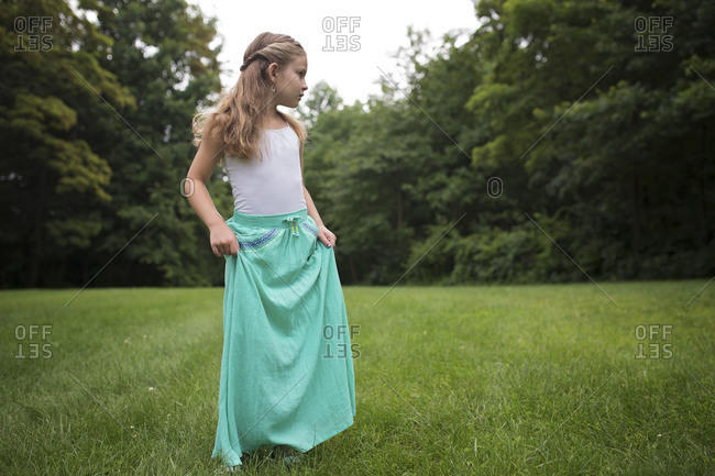 Girl in long skirt standing in lawn