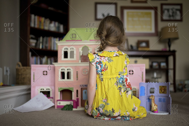 Little girl playing with dollhouse at home