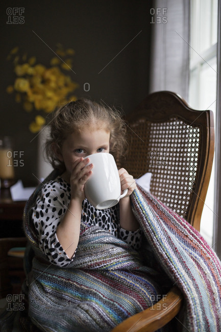 Little girl in blanket drinking from mug