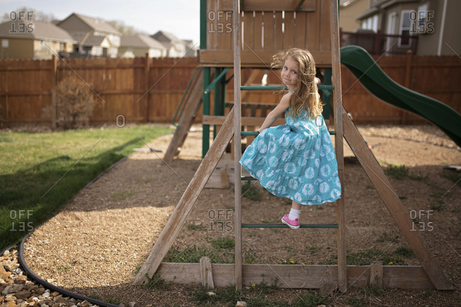 Little girl climbing jungle gym steps in yard