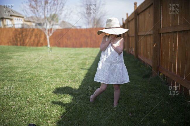 Little girl standing in shadows in backyard