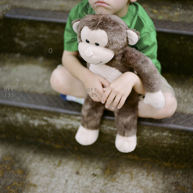 Tired little boy on steps with stuffed animal
