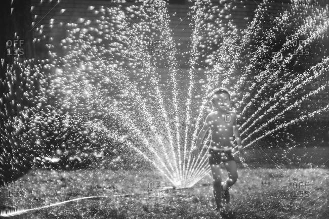 Little boy running through sprinkler in his yard
