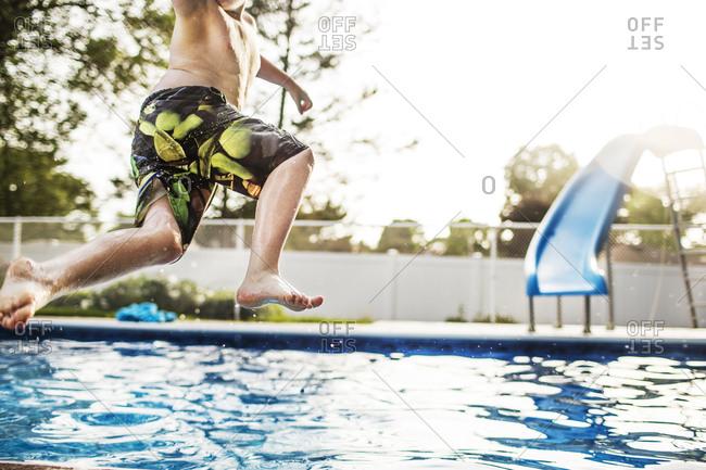 Boy midair jumping into swimming pool