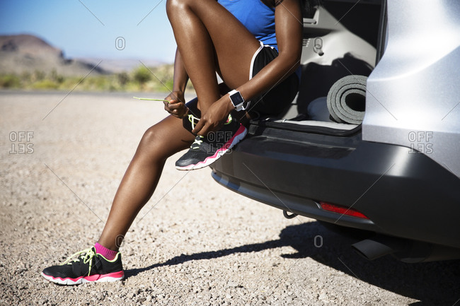 Athletic woman tying shoes in desert