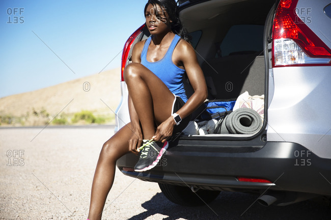 Woman sitting in van tying shoes for workout
