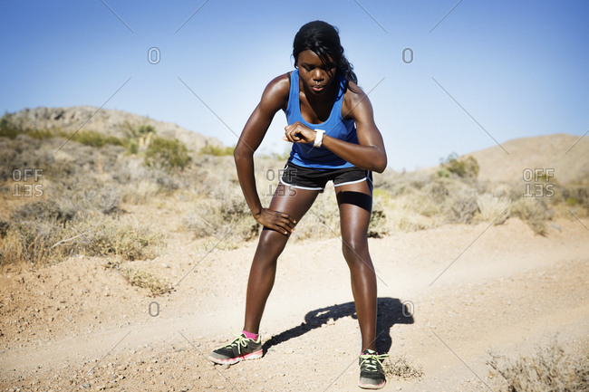 Athletic woman in remote setting checking watch