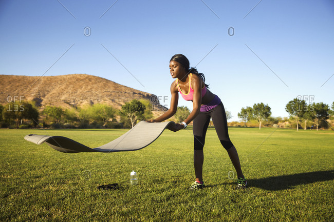 Athletic woman laying out yoga mat
