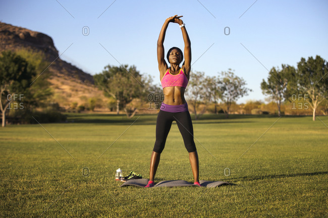 Athletic woman standing on yoga mat stretching