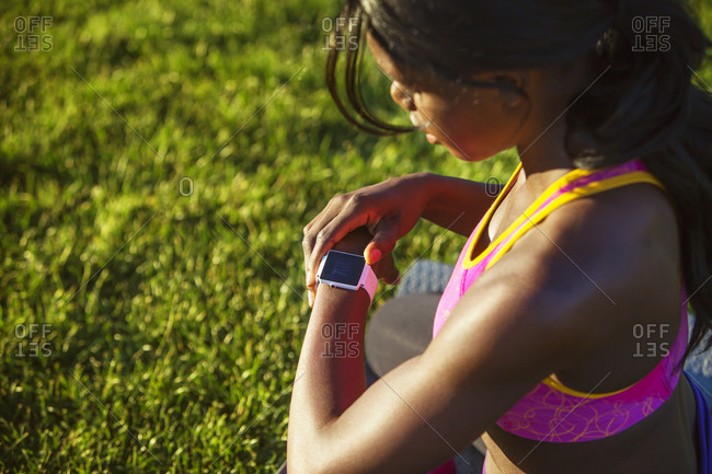 Athletic woman checking her fitness tracker