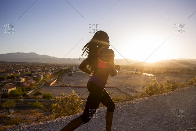 Woman running on mountain overlooking desert subdivision