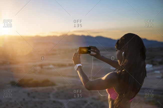 Athletic woman taking picture of desert setting