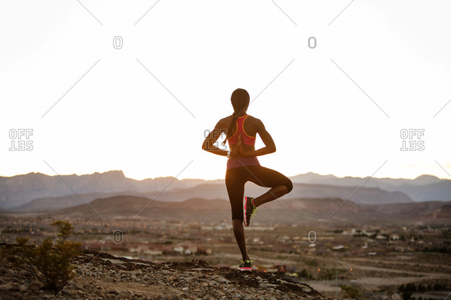 Woman on desert hill in yoga pose