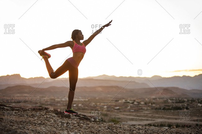Woman on desert hill in yoga stance